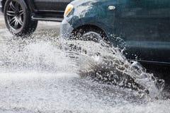 El coche salpica a través de un charco grande en una calle inundada Foto de archivo libre de regalías