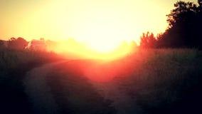 El coche se aleja en los rayos del sol naciente