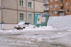 El coche se cubre con nieve, cerca a la casa Fotografía de archivo