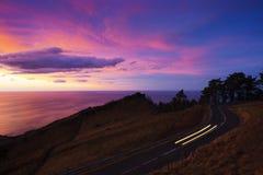 El coche se enciende en el camino del soporte Jaizkibel en la puesta del sol Fotos de archivo