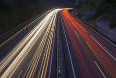 El coche se enciende en la noche en el camino en la carretera Fotografía de archivo libre de regalías