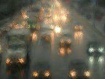 El coche se enciende en noche de la lluvia como impresionismo stylized Imagenes de archivo