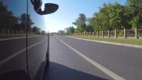El coche se mueve a lo largo de la calle de la ciudad a lo largo del parque en un día de verano soleado almacen de metraje de vídeo