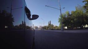 El coche se mueve a lo largo de la calle de la ciudad en un día de verano soleado almacen de video