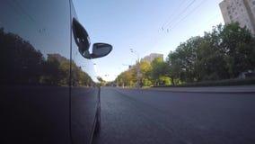 El coche se mueve a lo largo de la calle de la ciudad en un día de verano soleado metrajes