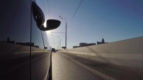 El coche se mueve a lo largo de la carretera de la ciudad en un día de verano soleado almacen de metraje de vídeo