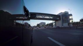 El coche se mueve a lo largo de la carretera de la ciudad en un día de verano soleado metrajes
