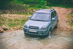 El coche se mueve a través del río de la montaña Fotos de archivo