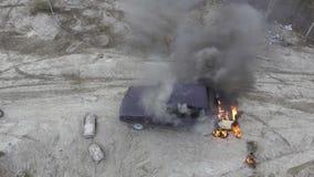El coche se pone en el fuego en campo abandonado del polvo con el humo negro enorme que sube en cielo metrajes