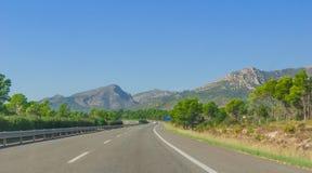 El coche solitario pasa abajo de la carretera a través de las colinas y de las montañas costeras de España rural Foto de archivo