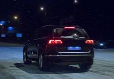 El coche va abajo de la calle en la noche del invierno Fotos de archivo libres de regalías