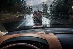El coche va bajo la lluvia Visi?n desde el interior Gotas de agua en el parabrisas Visibilidad pobre y conducción peligrosa imagen de archivo