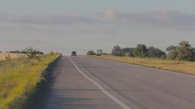El coche va en una carretera nacional entre los campos del pshenichnyh M?quina en la puesta del sol, contra un fondo del campo de almacen de metraje de vídeo