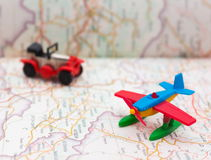 El coche y el aeroplano miniatura en mapa, viajan en todo el mundo Foto de archivo libre de regalías