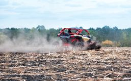 El cochecillo rojo acomete a través del campo en el polvo fotos de archivo libres de regalías