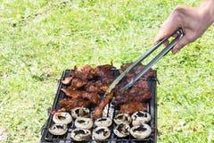 El cocinar al aire libre asado a la parrilla barbacoa de la mano de la comida de la carne Fotos de archivo libres de regalías