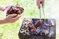 El cocinar al aire libre asado a la parrilla barbacoa de la mano de la comida de la carne Imagen de archivo