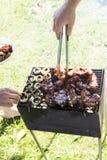 El cocinar al aire libre asado a la parrilla barbacoa de la mano de la comida de la carne Foto de archivo libre de regalías