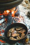 El cocinar al aire libre en un cuenco de acero inoxidable sobre un fuego ardiente Fotografía de archivo
