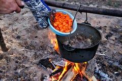 El cocinar al aire libre Fabricación de la comida en un fuego en un pote Imagen de archivo libre de regalías