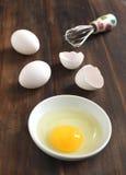 El cocinar, bate con los huevos en cáscaras de un tazón de fuente y de huevo Imágenes de archivo libres de regalías
