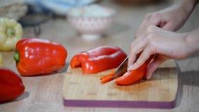 El cocinar, comida y concepto casero - cercanos para arriba de la pimienta masculina del corte de la mano en tabla de cortar en c metrajes