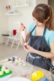 El cocinar, comida y concepto que cuece - cocinero con el bolso de la confitería que exprime la crema que llena a los macarons cá imagen de archivo libre de regalías