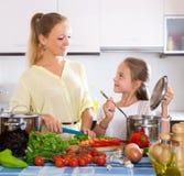 El cocinar de la madre y de la niña Fotos de archivo libres de regalías