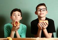 El cocinar de los escolares del adolescente come el perrito caliente Fotos de archivo libres de regalías