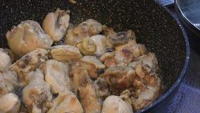 El cocinar de los pedazos del pollo en un sartén almacen de video