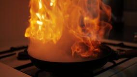 El cocinar en cacerola del wok con el fuego duro que quema en la c?mara lenta metrajes