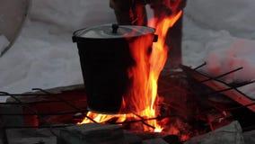 El cocinar en el fuego cacerola sobre una llama abierta metrajes
