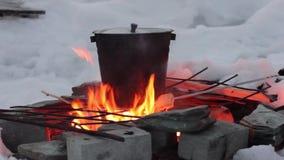 El cocinar en el fuego cacerola sobre una llama abierta almacen de metraje de vídeo