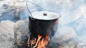 El cocinar en un fuego almacen de metraje de vídeo