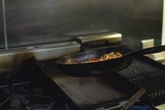 El cocinar en una cebolla del restaurante y una pimienta roja fotografía de archivo
