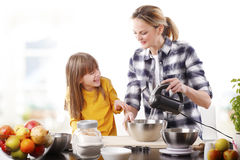 El cocinar feliz de la madre y de la hija del cutie Foto de archivo libre de regalías