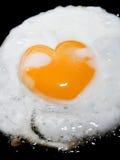 El cocinar friendo el huevo con el corazón forma la yema de huevo en negro Foto de archivo libre de regalías