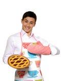 El cocinar. Hombre joven en empanada sabrosa cocida al horno delantal Imagen de archivo