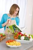 El cocinar - libro de cocina de la lectura de la mujer en cocina Imagenes de archivo