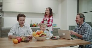 El cocinar maduro de la mujer feliz en la mañana para sus miembros de la familia entonces trae la comida en la tabla de cena y fe almacen de video