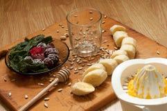 el cocinar, mano exprime el zumo de naranja, el plátano, las zarzamoras congeladas de las fresas y los ingredientes y la licuador Imágenes de archivo libres de regalías