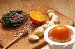 el cocinar, mano exprime el zumo de naranja, el plátano, las zarzamoras congeladas de las fresas y los ingredientes y la licuador Imagen de archivo libre de regalías