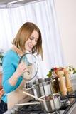 El cocinar - mujer feliz por la estufa en cocina fotos de archivo libres de regalías