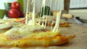 El cocinar, parte del sistema Tomando un pedazo de pizza hecha en casa recientemente cocida con estirar el queso 4K se cierran en almacen de metraje de vídeo