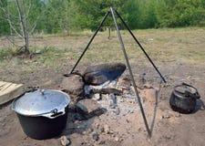 El cocinar sobre una hoguera en condiciones de campo Imagen de archivo libre de regalías