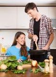 El cocinar sonriente de la mujer y del hombre Foto de archivo libre de regalías