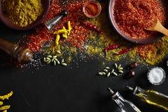 El cocinar usando las especias de tierra frescas con los cuencos grandes y pequeños de especia en una tabla negra con derramamien Imágenes de archivo libres de regalías