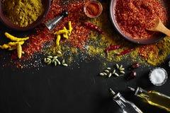 El cocinar usando las especias de tierra frescas con los cuencos grandes y pequeños de especia en una tabla negra con derramamien Fotos de archivo libres de regalías