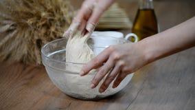 El cocinar y concepto casero - cercanos para arriba de las manos femeninas que amasan la pasta en casa almacen de metraje de vídeo
