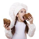 El cocinar y concepto de la gente - niña sonriente en sombrero del cocinero Foto de archivo libre de regalías
